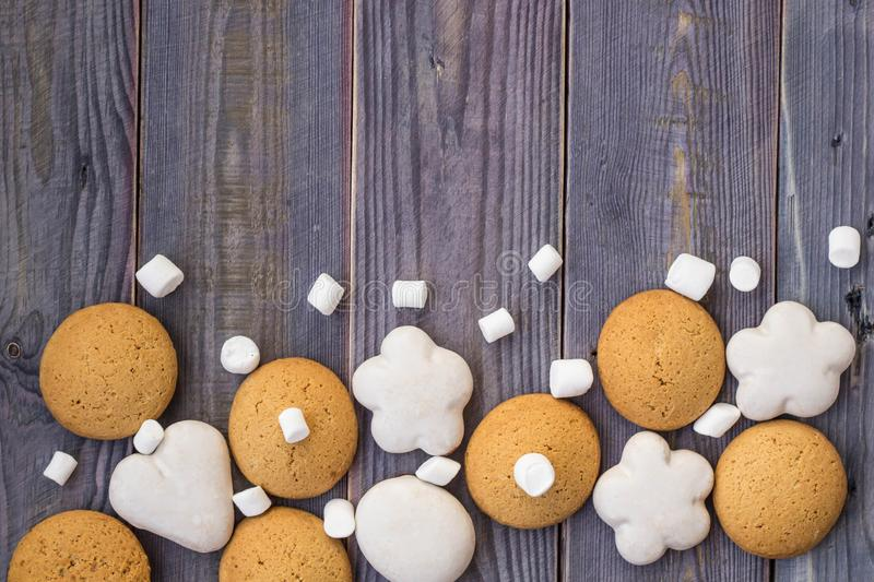 Border of white and brown gingerbread with marshmallows on wooden background.  stock images