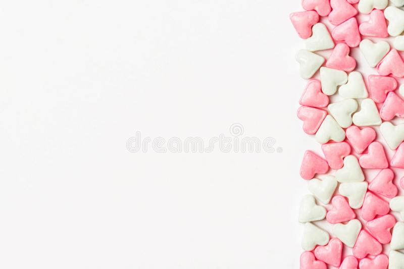 Border from white and pink sugar candy hearts on solid background. Valentine romantic love concept. Greeting card poster banner stock photo