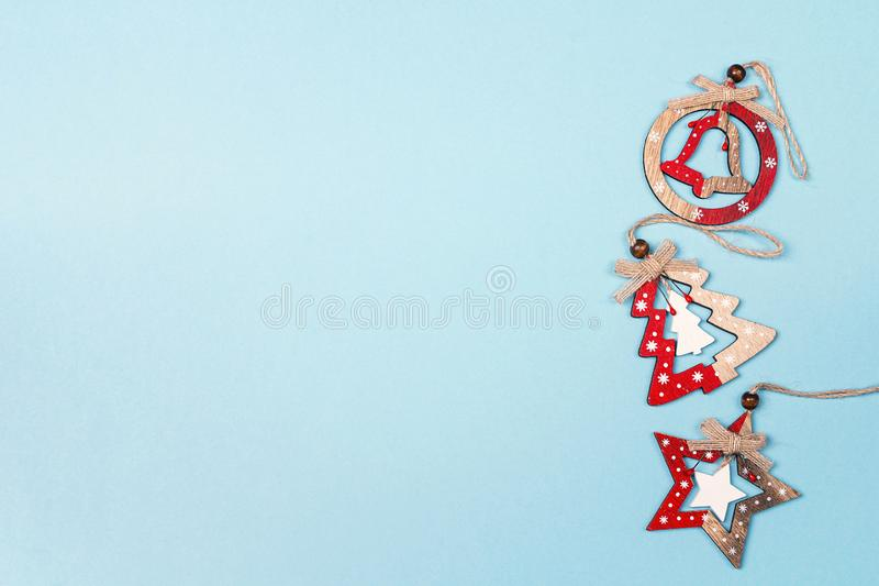 Border of wooden Christmas decorations on blue background with copy space. Top view, flat lay royalty free stock images