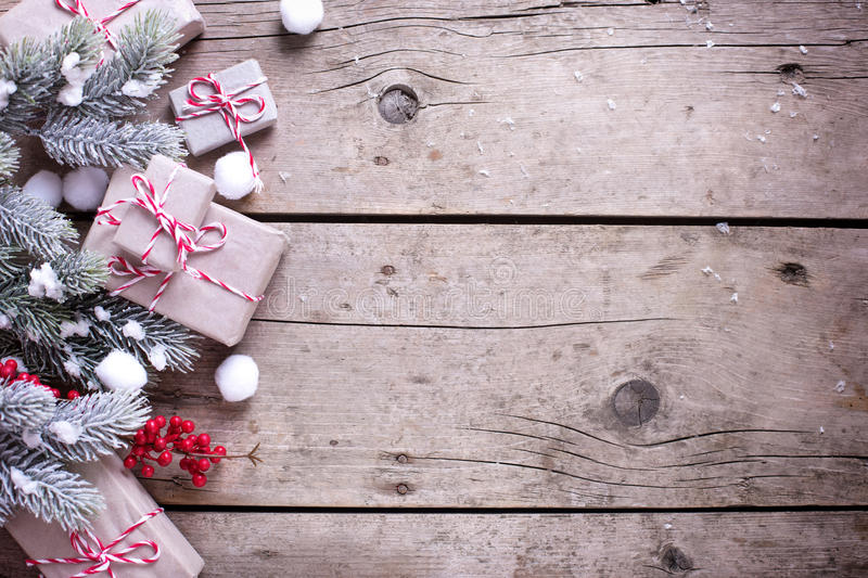 Border from wrapped christmas presents, fur tree branches, red b. Erries on aged wooden background. Selectife focus. Place for text stock photos
