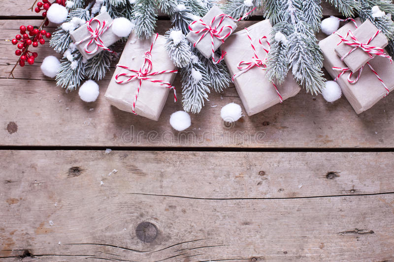 Border from wrapped christmas presents, fur tree branches, red b. Erries on aged wooden background. Selectife focus. Place for text stock image