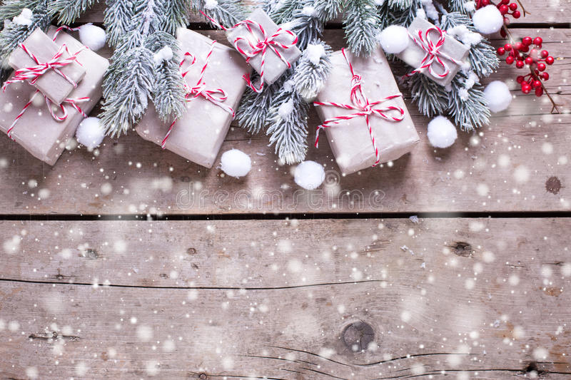 Border from wrapped christmas presents, fur tree branches, red b. Erries on aged wooden background. Selectife focus. Place for text. Drawn snow royalty free stock images