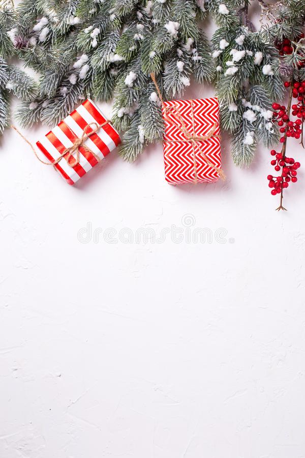 Border from wrapped christmas presents, fur tree branches, red b. Erries on white textured background. Selectife focus. Place for text. Flat lay stock photos