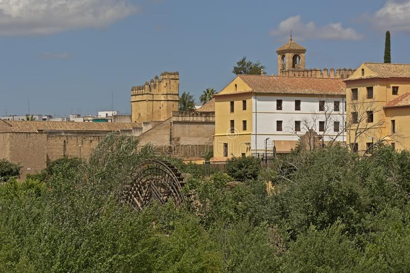 Green borders of Guadalqiovor rviver with historical waterwheel in Cordoba. Borders of Guadalqiovor river with historical Molino de la Albolafia waterwheel in royalty free stock photography