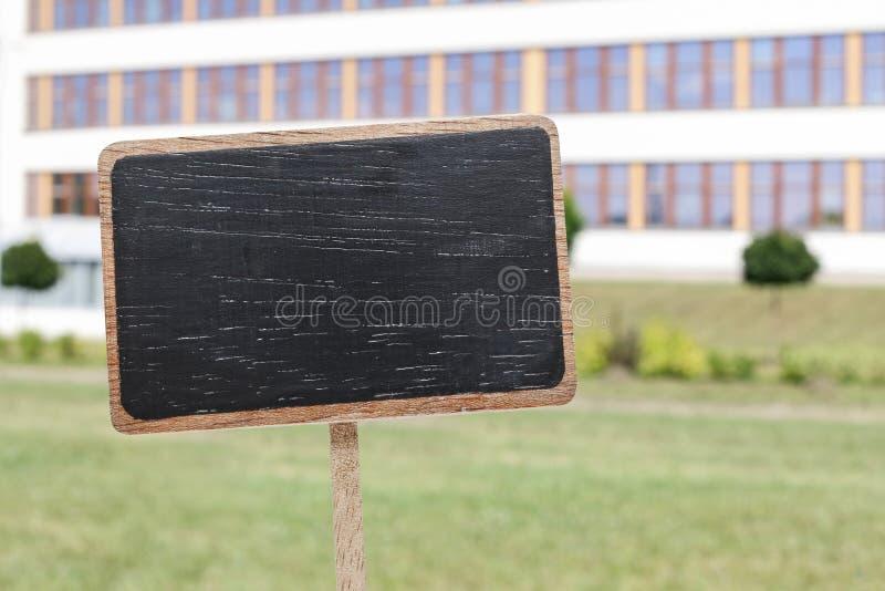 Bordetiket en een lage schoolgebouw in backgrou stock foto