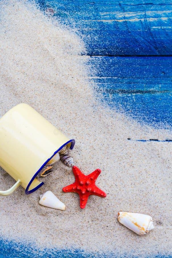Bordi blu sparsi sabbia variopinta della tazza delle coperture fotografia stock libera da diritti