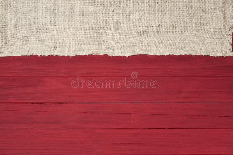 Bordi di legno rossi rustici nella disposizione piana con il tessuto della tela da imballaggio del bianco sporco dal lato superio fotografia stock
