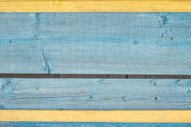 Bordi incrinati dipinti invecchiati con la pittura blu e gialla della sbucciatura di colore Il vecchio lerciume naturale ha strut immagine stock libera da diritti