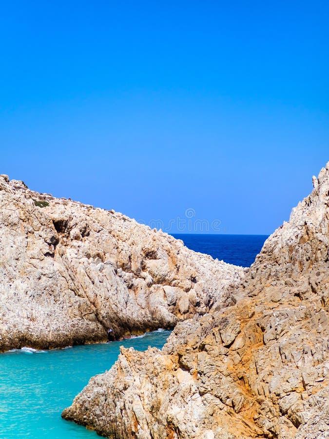 Bordi rocciosi taglienti e belle tonalità differenti delle acque di mare blu di Creta, Grecia fotografie stock
