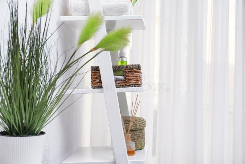 Bordlägga enheten med rena handdukar och skönhetsmedel i badrum fotografering för bildbyråer