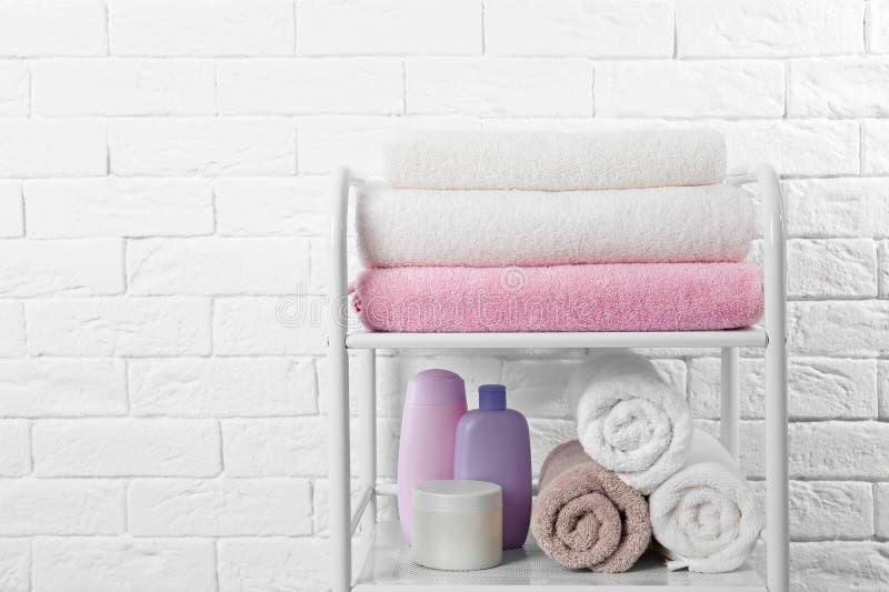 Bordl?gga enheten med rena handdukar och toalettartiklar n?ra tegelstenv?ggen royaltyfri bild