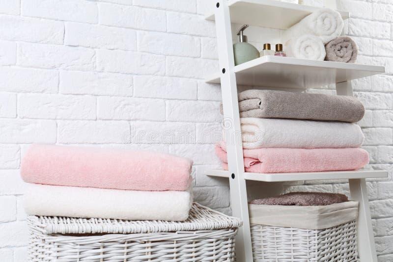 Bordlägga enheten och korgar med rena handdukar och toalettartiklar arkivfoto