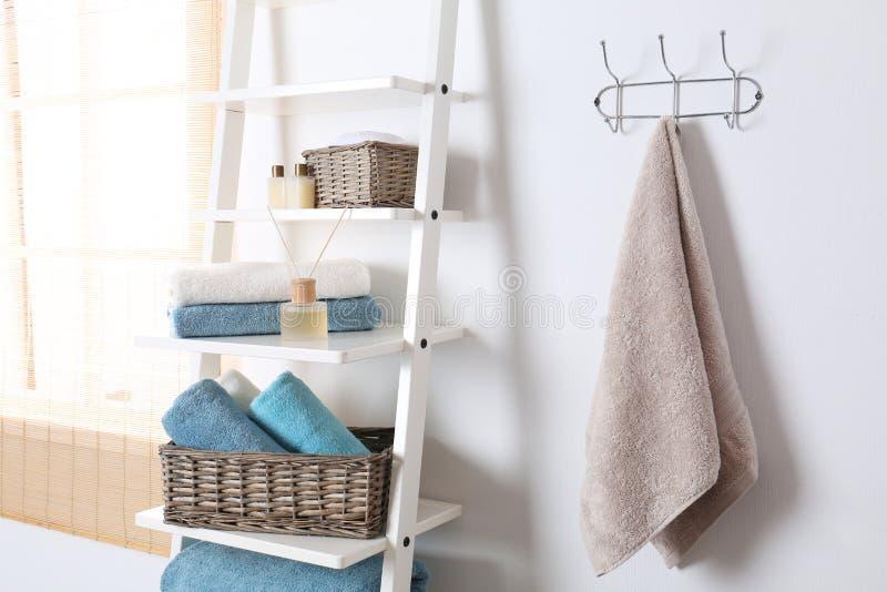 Bordlägga enheten och kuggen med rena handdukar och toalettartiklar arkivfoton