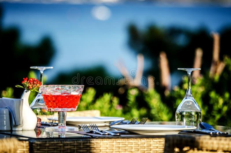 Bordlägga inställningen för matställe i en restaurang på stranden royaltyfria bilder