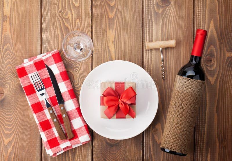 Bordlägga inställningen med gåvaasken på plattan, vinexponeringsglas och rött vin bo fotografering för bildbyråer