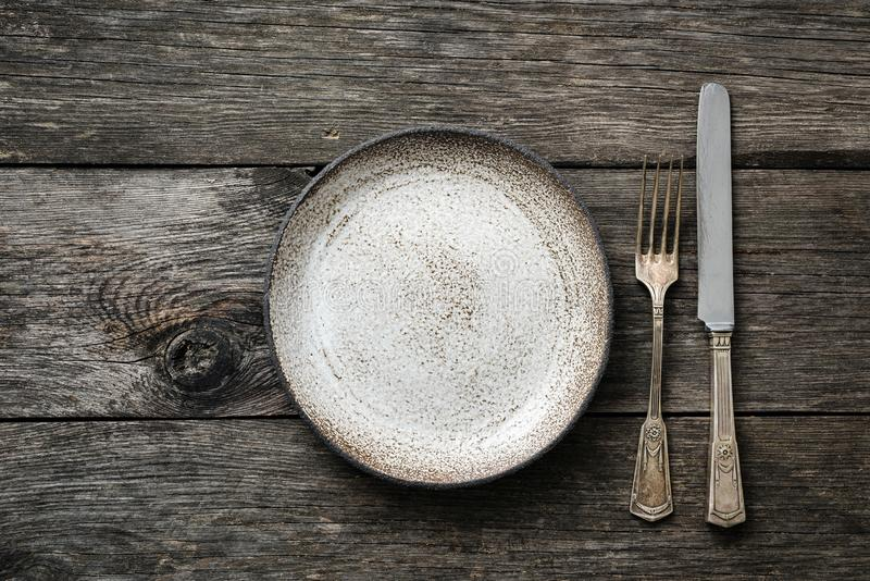 Bordlägga inställningen med tappningbestick eller bestick och töm plattan på lantligt trä arkivfoto