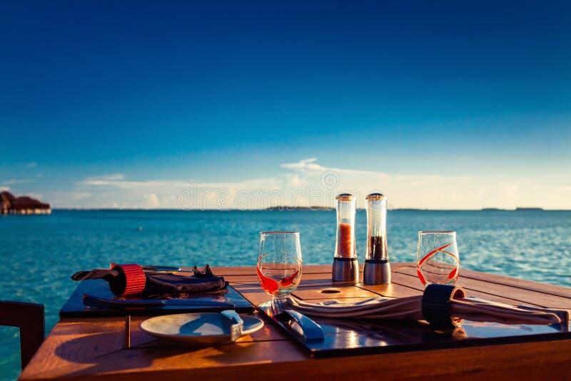 Bordlägga inställningen på den tropiska strandrestaurangen under solnedgång royaltyfri foto