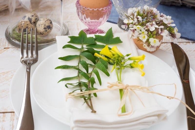 Bordlägga inställningspåsken, vitplattor, servetten, buketten av nya gula blommor, vaktelägg arkivbild