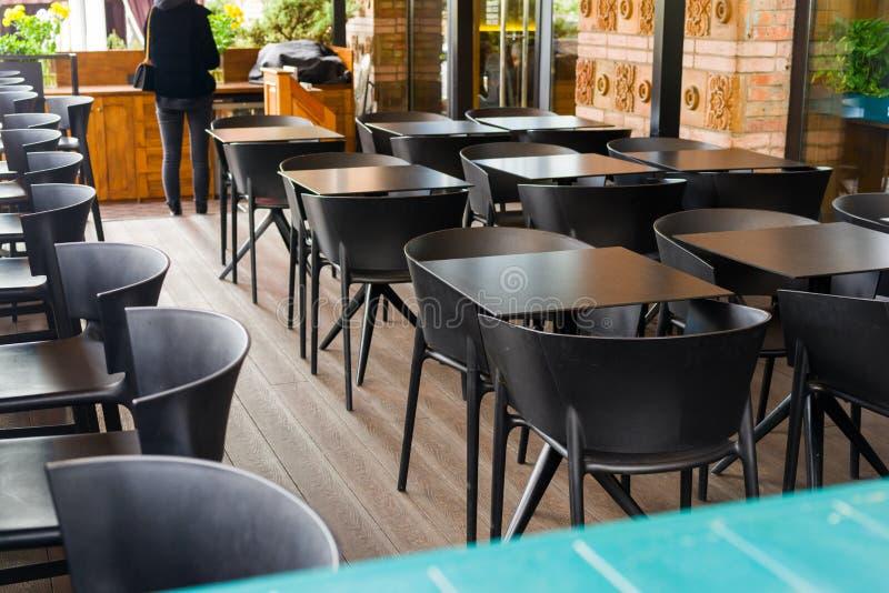 Bordlägger och stolar i en cafe arkivbild