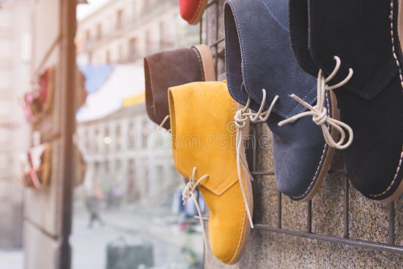Bordlägger tillfälliga skor hänger väggen av shoppar framme arkivfoto