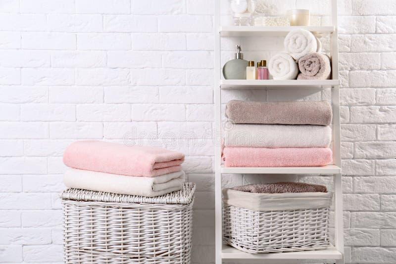 Bordl?gga enheten och korgar med rena handdukar och toalettartiklar royaltyfri bild