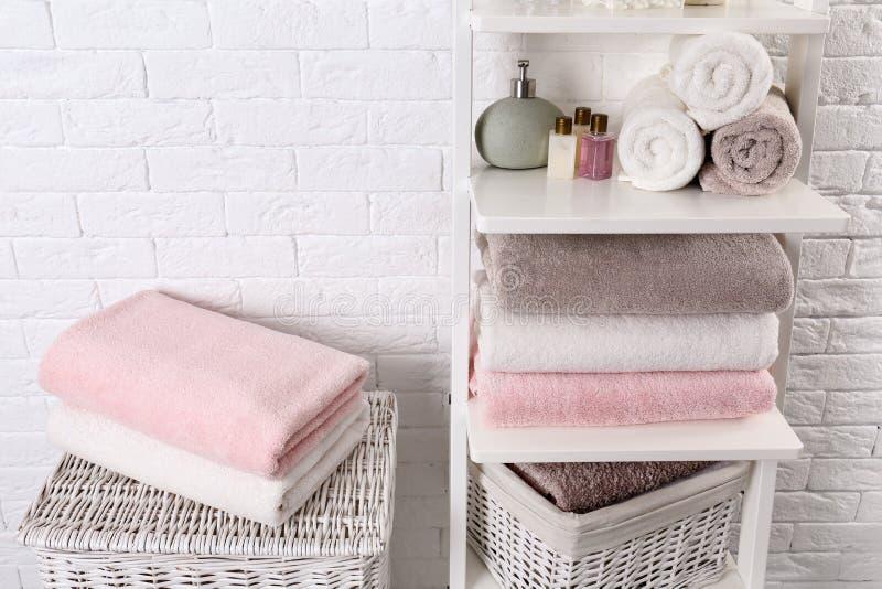 Bordl?gga enheten och korgar med rena handdukar och toalettartiklar arkivfoton
