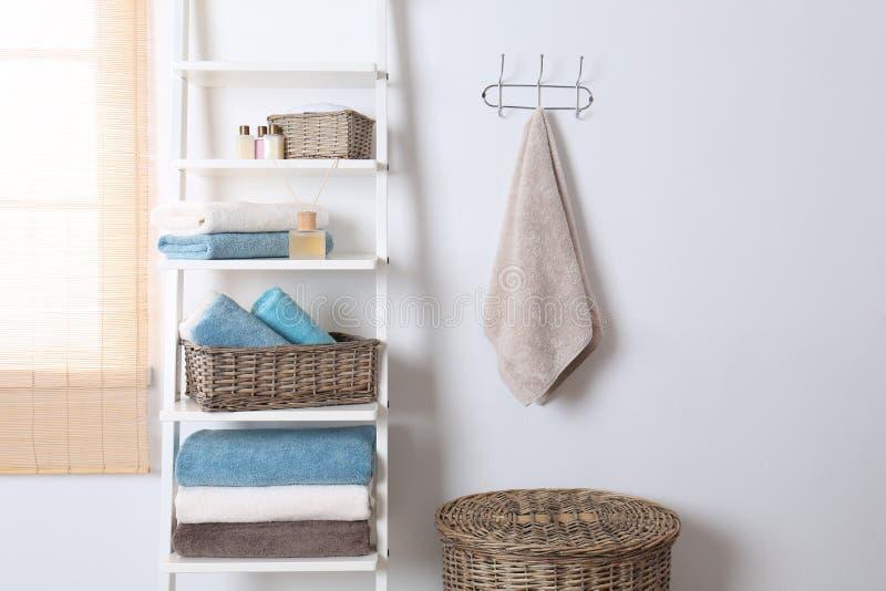Bordl?gga enheten och kuggen med rena handdukar och toalettartiklar royaltyfri foto