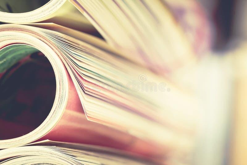 Bordo alto vicino della rivista variopinta che impila rotolo con il fondo confuso dello scaffale per libri per il bublication e c immagine stock libera da diritti