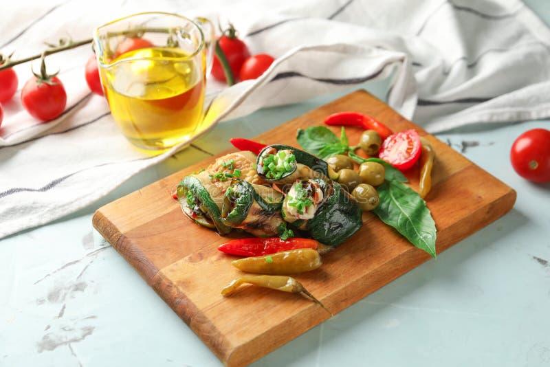 Bordo con i rotoli e le verdure saporiti dello zucchini sulla tavola leggera fotografie stock libere da diritti