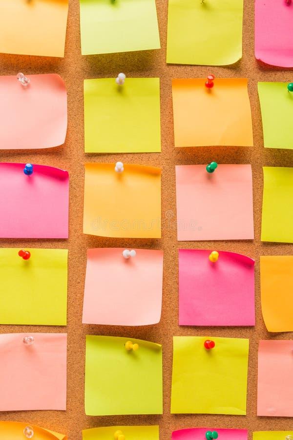 Bordo con le note in bianco colorate appuntate - immagine del sughero fotografia stock