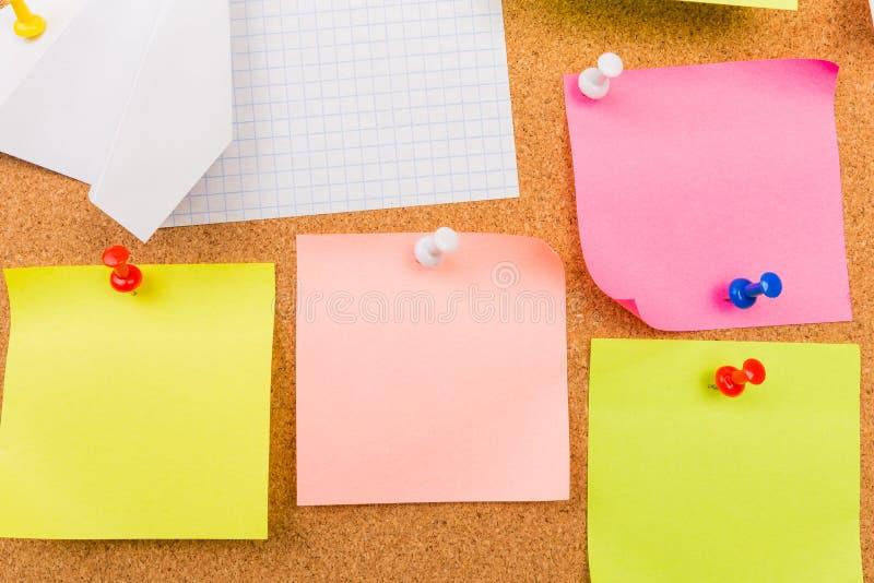Bordo con le note in bianco colorate appuntate - immagine del sughero fotografie stock libere da diritti