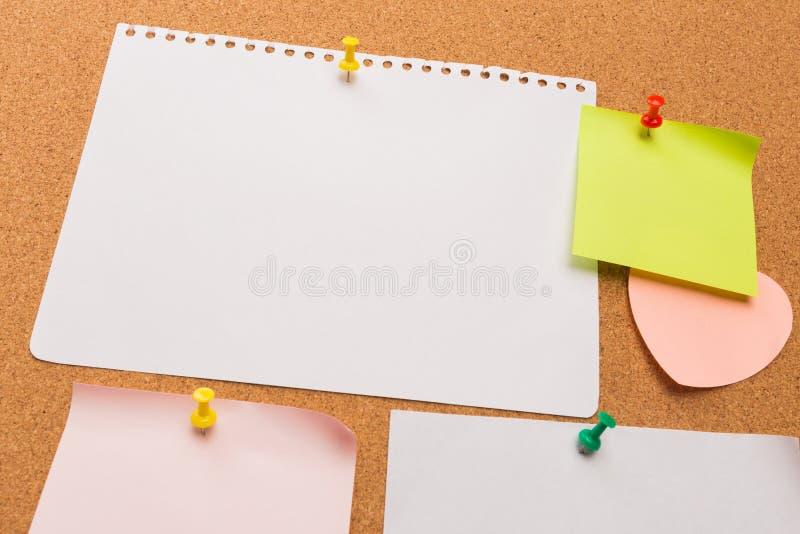 Bordo con le note in bianco colorate appuntate - immagine del sughero immagini stock