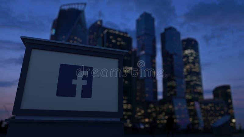 Bordo del contrassegno della via con il logo di Facebook nella sera Fondo vago dei grattacieli del distretto aziendale 3D editori immagini stock