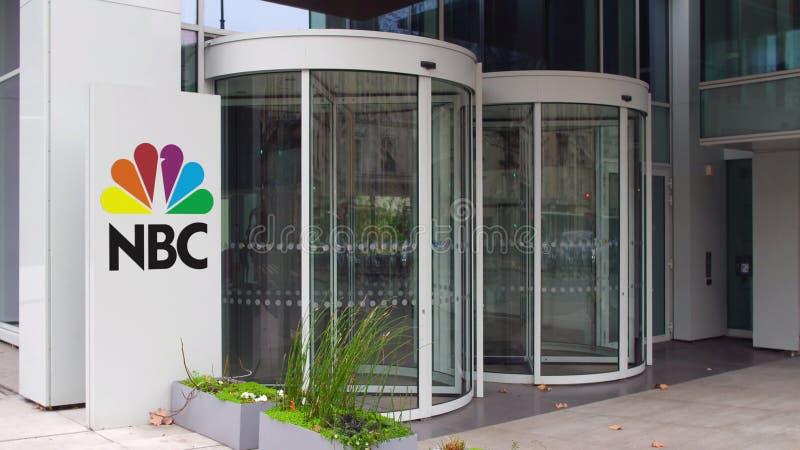 Bordo del contrassegno della via con il logo di NBC di National Broadcasting Company Edificio per uffici moderno Rappresentazione immagine stock libera da diritti