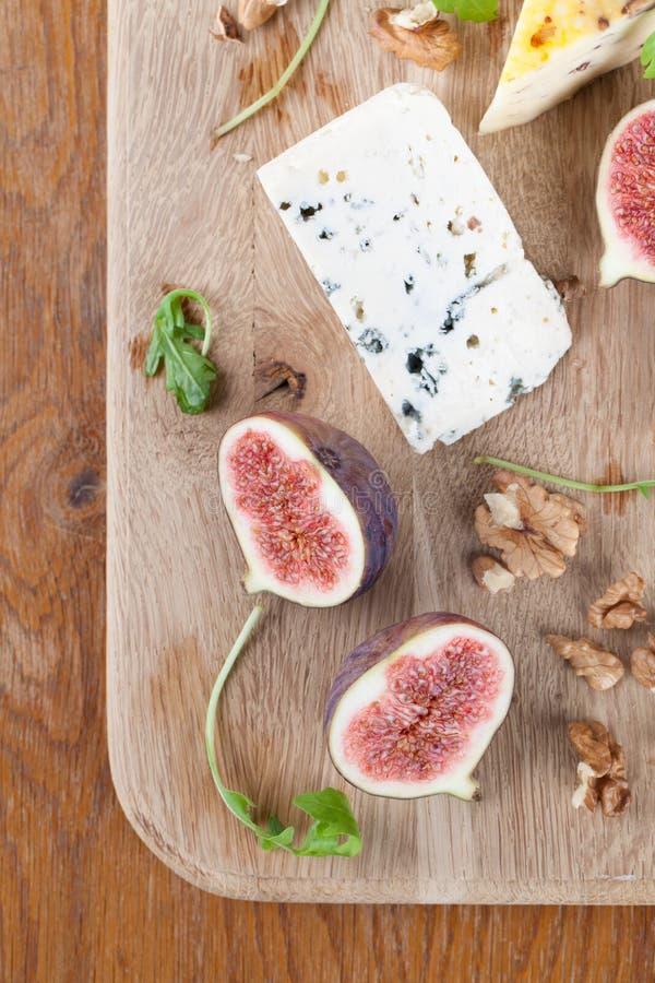 Bordo del formaggio con i fichi ed i dadi immagini stock