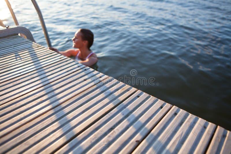 Bordo del pilastro con la donna in acqua fotografia stock libera da diritti