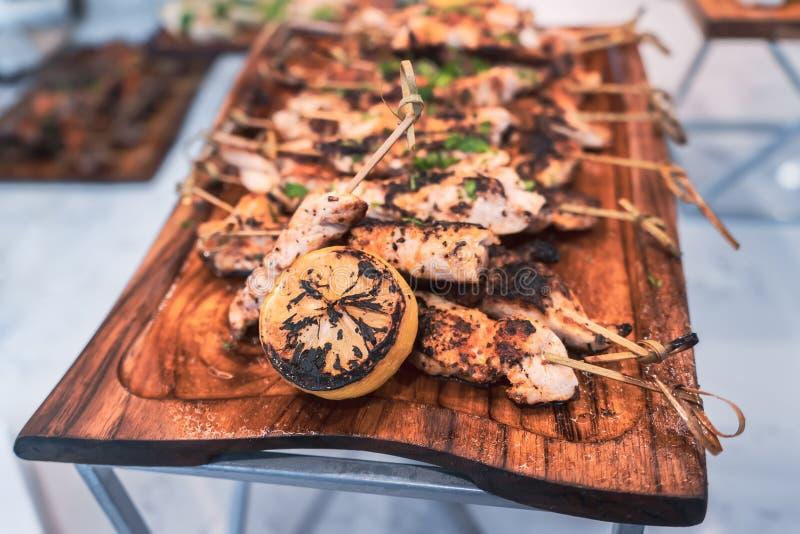 Bordo delizioso degli spiedi del pollo serviti con il limone arrostito fotografia stock