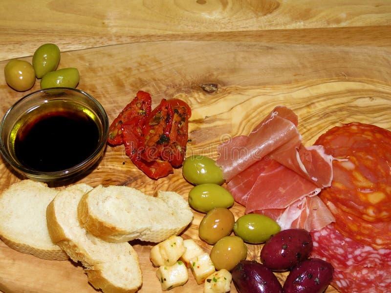 Bordo dell'antipasto con una selezione delle carni, olive, formaggio, toma fotografia stock