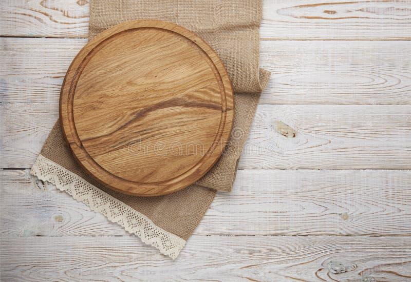 Bordo della pizza, tovagliolo della tela con pizzo sulla tavola di legno Derisione di vista superiore su fotografia stock