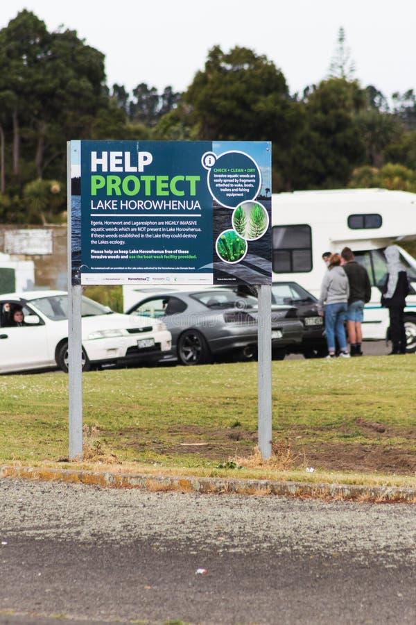 Bordo di informazioni inviato nel lago Horowhenua che istruisce gli ospiti sui pericoli di diffusione delle erbacce acquatiche di fotografia stock libera da diritti