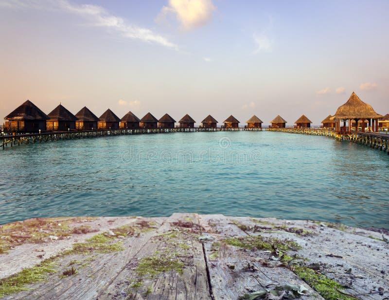 Bordo di legno d'annata con il mare, la spiaggia e le casette sopra il fondo dell'acqua fotografia stock