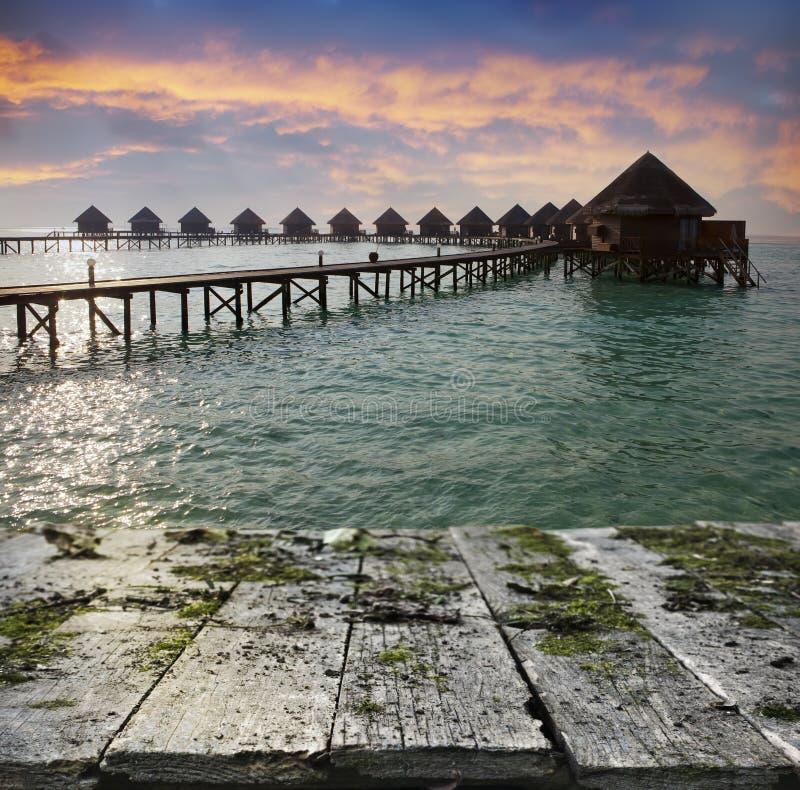Bordo di legno d'annata con il mare, la spiaggia e le casette sopra il fondo dell'acqua fotografia stock libera da diritti
