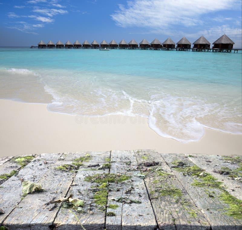 Bordo di legno d'annata con il mare, la spiaggia e le casette sopra il fondo dell'acqua fotografie stock