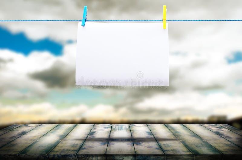 Bordo di legno nella prospettiva, contro lo sfondo di un cielo vago e di un foglio bianco di carta su una corda fotografie stock libere da diritti