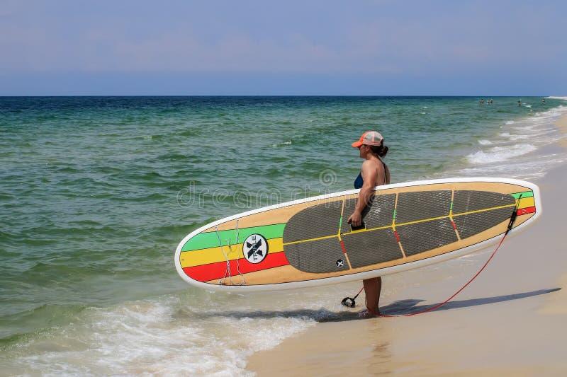 Bordo di pagaia di triplo X della tenuta del surfista sulla spiaggia fotografia stock libera da diritti