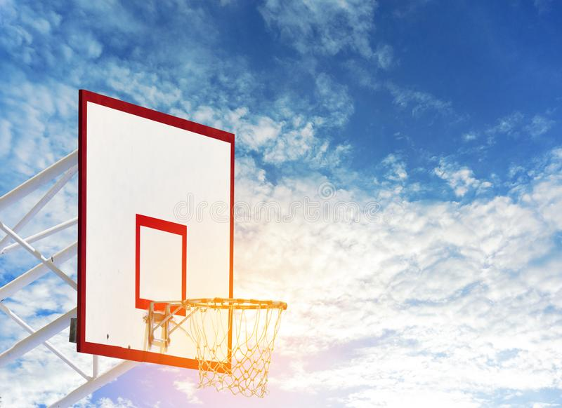 Bordo di pallacanestro con la rete del cerchio alla terra del gioco della palla del canestro il giorno soleggiato con chiaro ciel fotografia stock libera da diritti
