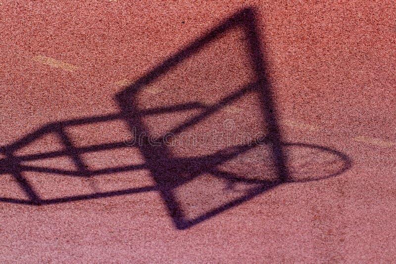 Bordo di pallacanestro ed ombra della rete sulla terra del campo da pallacanestro fotografie stock