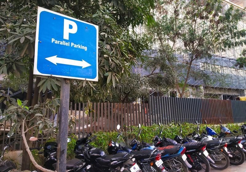 bordo di parcheggio parallelo del segno con parallelo parcheggiato due carrai immagine stock libera da diritti