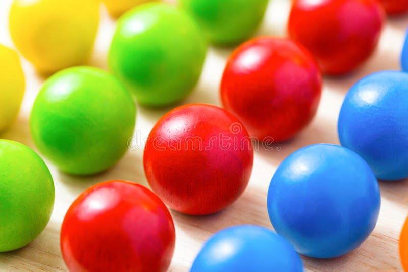 Bordo di pioli colorato, perle di legno su fondo di legno DOF basso immagine stock