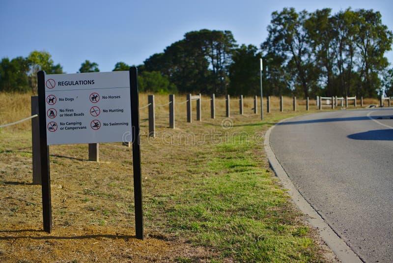 Bordo di regolamento del parco dal lato della via fotografia stock libera da diritti
